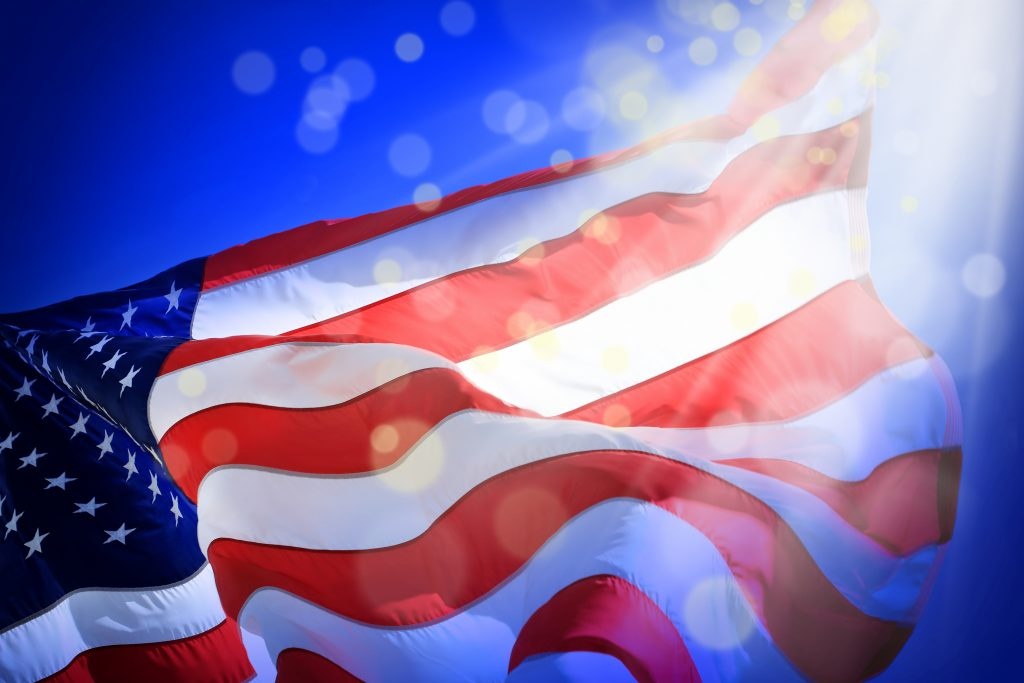 Conceptual image of waving American flag and light beam with abstract lights over blue background