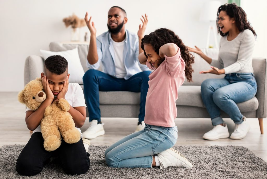 Family Conflicts. Sad little black children covering ears with hands while their parents arguing in the background, upset boy and girl dont want to hear quarrel, stressed kid sitting on the floor