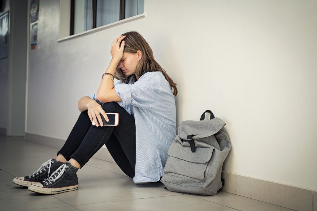 Upset and depressed girl holding smartphone sitting on college campus floor holding head. University sad student suffering from depression sitting on floor at high school. Lonely bullied teen.
