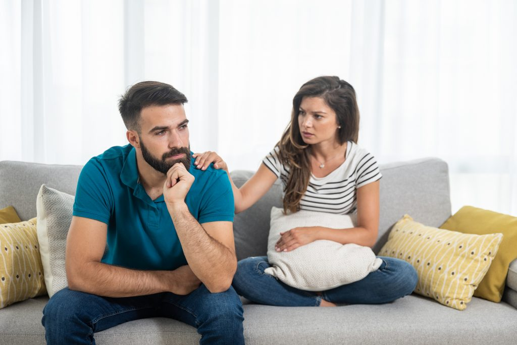 Young couple woman and man sitting on the sofa in the living room had an argue and not talking where girlfriend put her hand on the boyfriend shoulder and try to calm him down, relationship issues