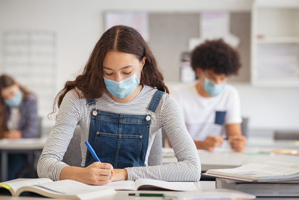 High school student taking notes while wearing face mask due to coronavirus.