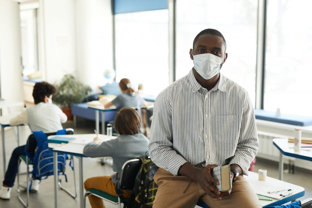 African-American teacher wearing mask in school classroom and looking at camera, stressed teacher.