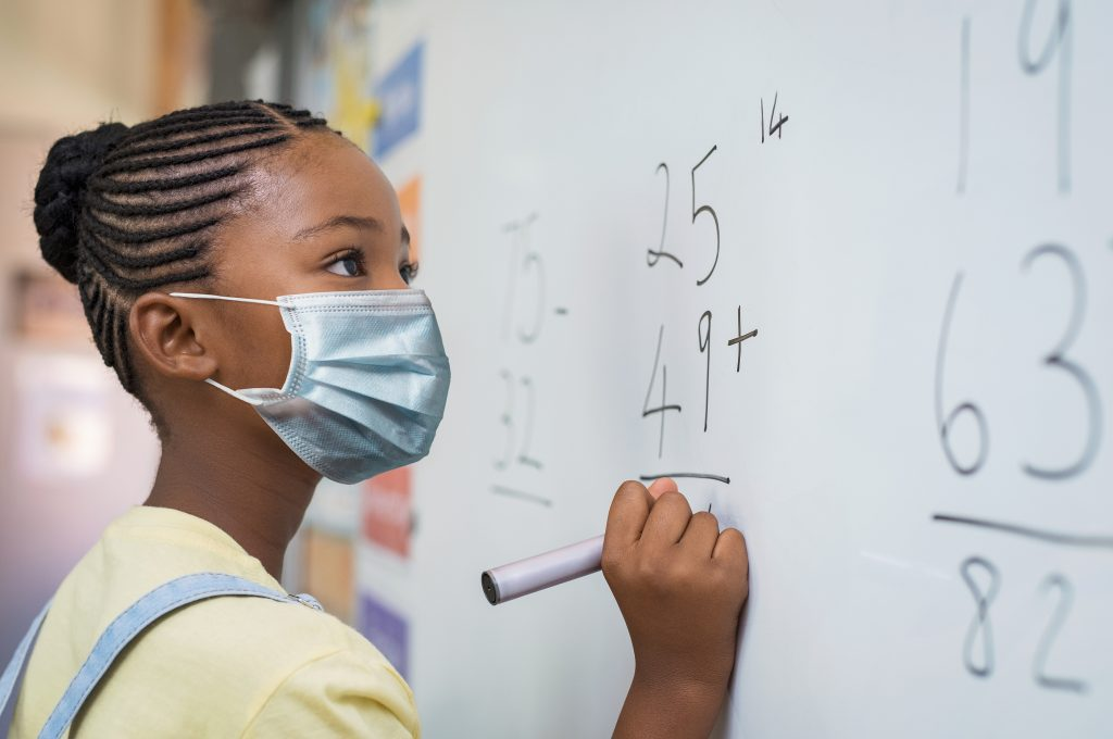 Portrait of african girl wearing face mask and writing solution of sums on white board at school. Black schoolgirl solving addition sum on white board during Covid-19 pandemic. School child thinking.