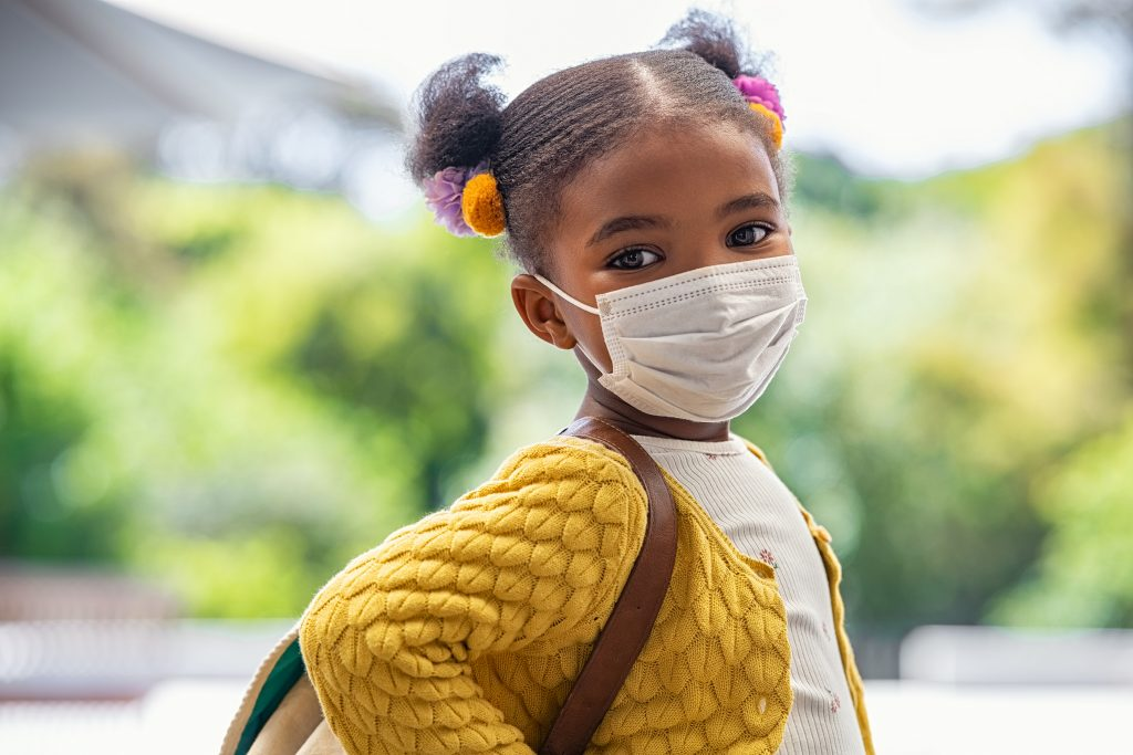 Smiling cute little girl with school backpack and protective face mask ready for first day of school during covid pandemic.