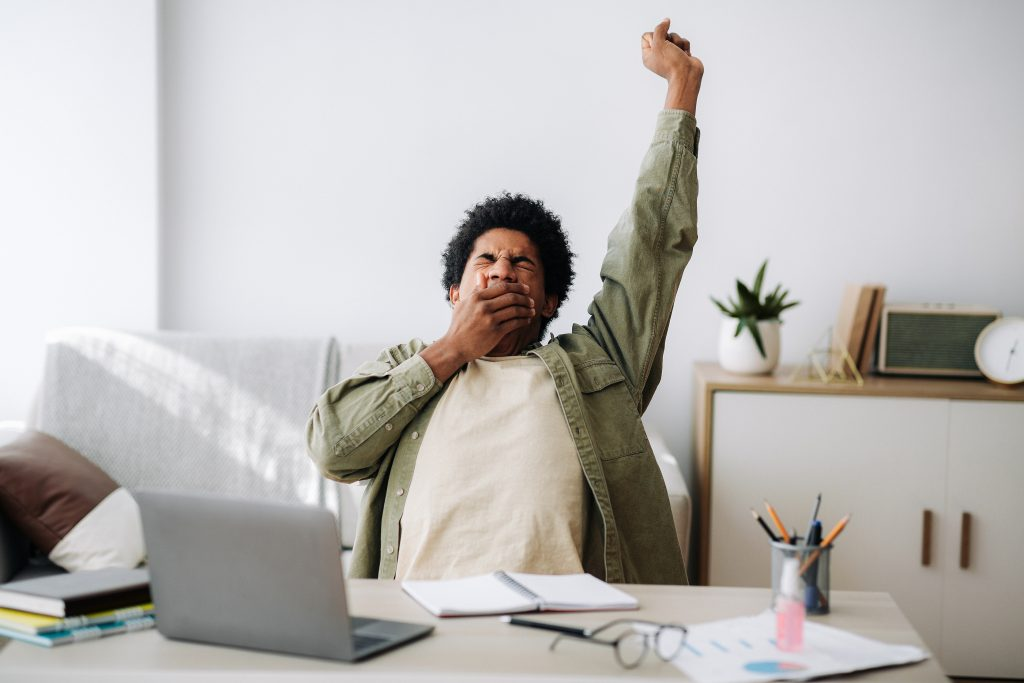 Tired black student yawning and stretching during his remote studies from home. African American youth exhausted from getting ready for test or writing coursework, feeling sleepy in front of laptop