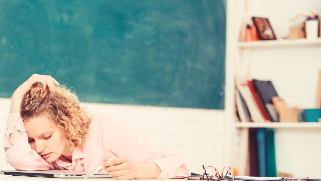 Tired tutor fall asleep at workplace. Tired student lean on desk. Exhausting lesson. Teacher exhausted after hard working day. Woman tired in school classroom. School pedagogue stressful occupation