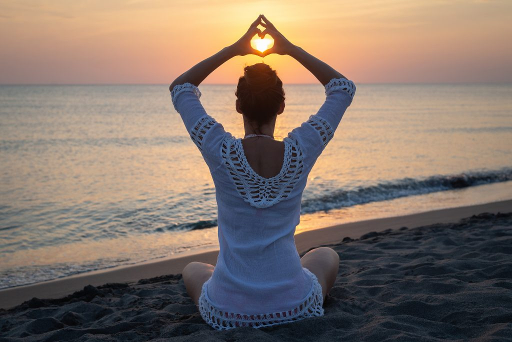 Woman doing yoga on beach in sunset. healthy lifestyle. Happy people.