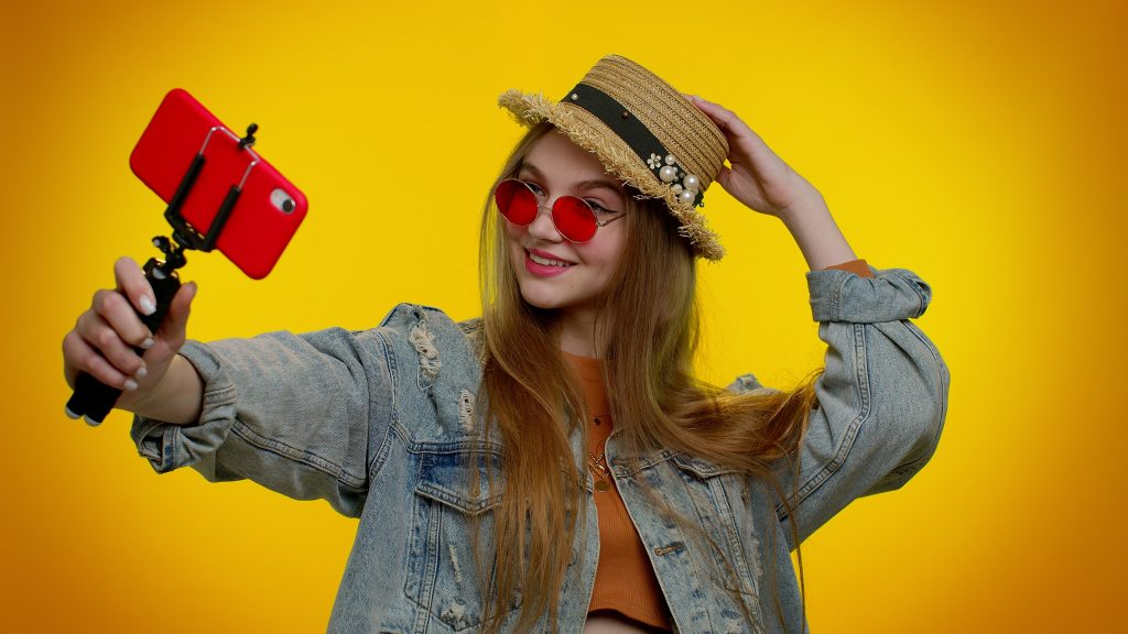 Beautiful teenager student girl traveler blogger in sunglasses, taking selfie on mobile phone, communicating video call online with family. Young fashionable woman on yellow studio wall background