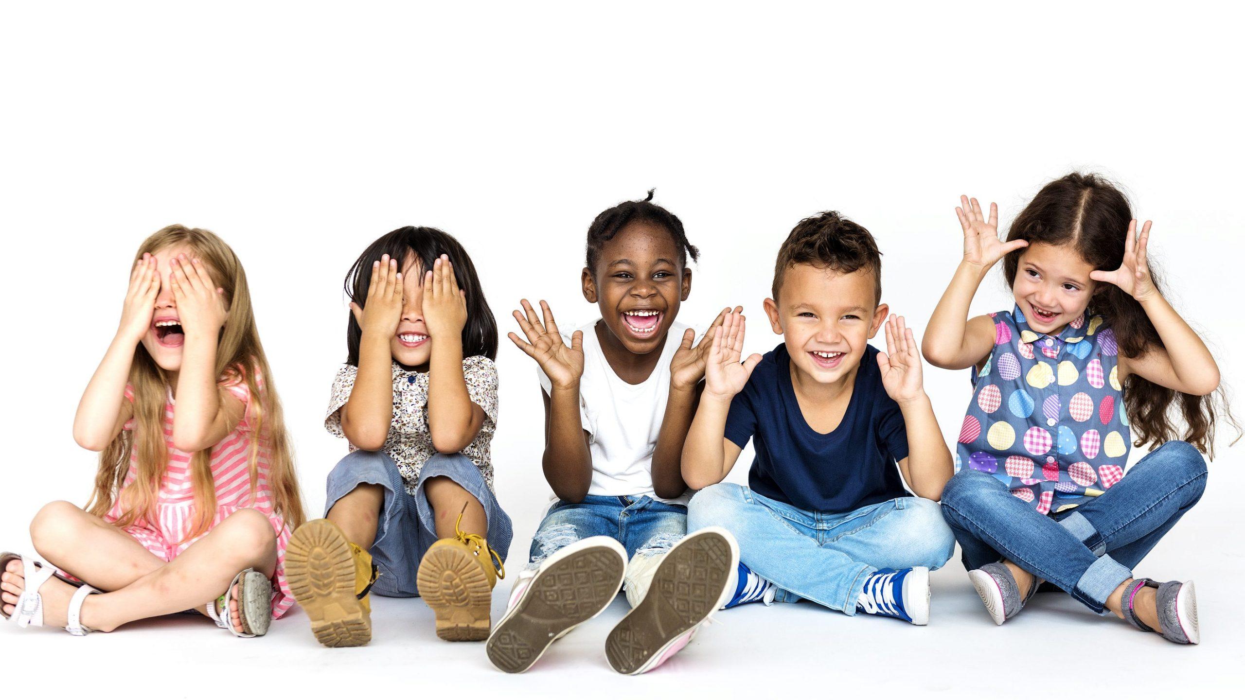 Diverse group of children doing peek a boo hand gesture