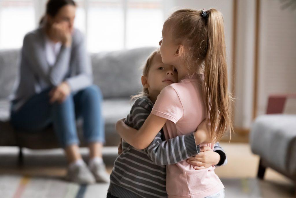 Empathic elder sister cuddling comforting little brother after family quarrel.
