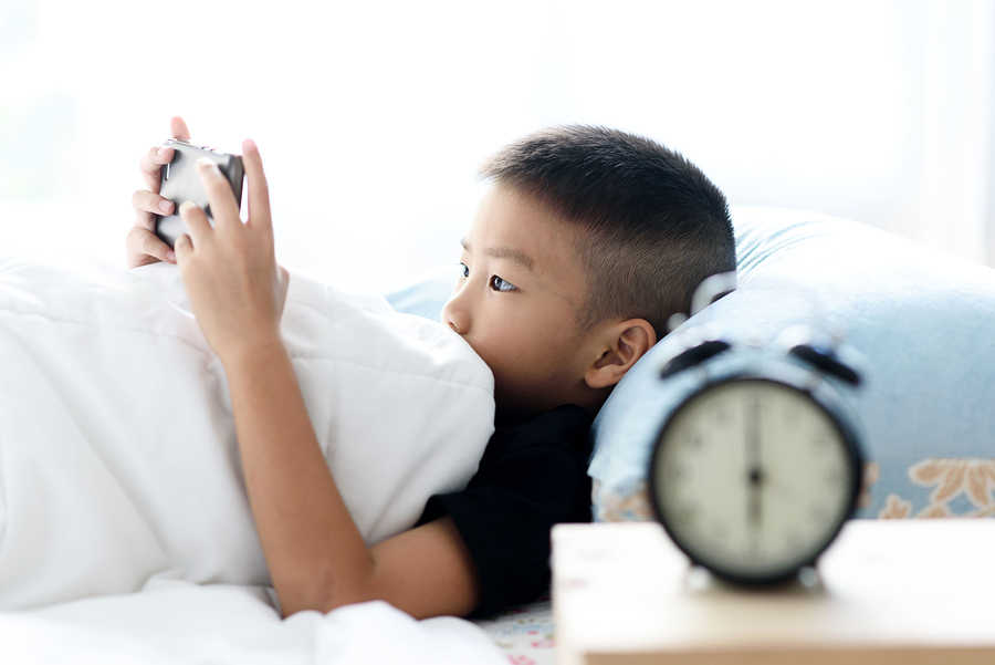 Selective focus at young Asian boy using cell phone on bed in the morning light with out focus vintage alarm clock.