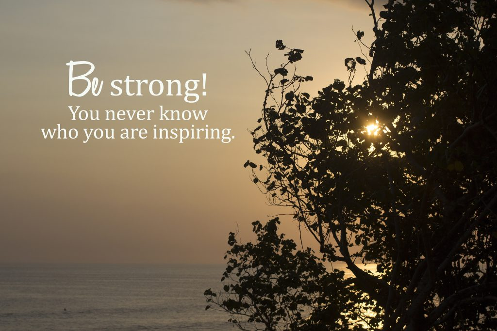 Inspirational motivational quote - Be strong. You never know who you are inspiring. With sunset over the sea horizon and the sun behind the tree silhouette. Be inspire concept.